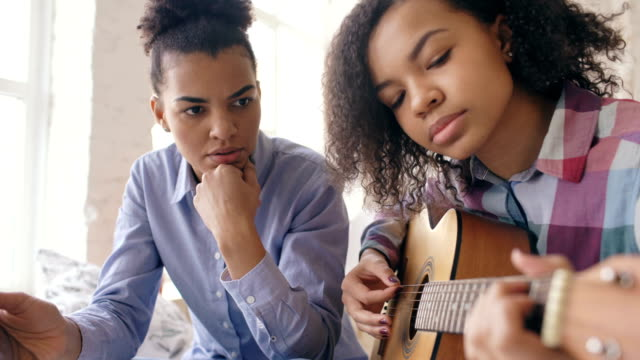 Mixed race young woman with tablet computer sitting on bed teaching her teenage sister to play acoustic guitar at home video