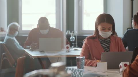 vidéos et rushes de femme raced mélangée dans le masque de visage travaillant sur l'ordinateur portatif dans le bureau - bureau ameublement