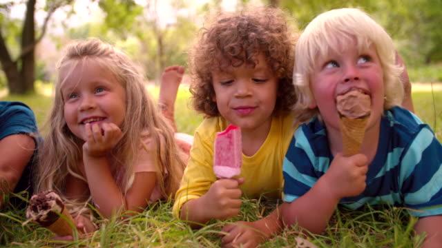 vídeos y material grabado en eventos de stock de mezclada raza grupo de niños amigos a comer helados - ice cream