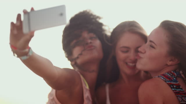Mixed racial group of friends laughing and pulling faces while taking a selfie on a phone at the beach video
