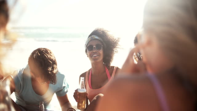 Mixed racial group of friends relaxing with beer on beach video