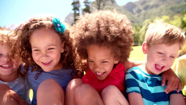 Mixed racial group of kid friends sitting together video