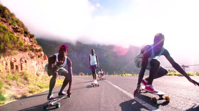 Mixed racial group of teen longboarders on road video