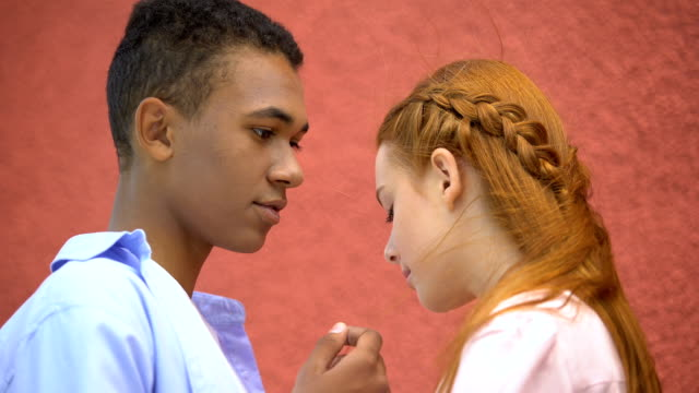 mixed-race boyfriend tenderly holding girlfriends chin, moment of first kiss - kids kiss embarrassed video stock e b–roll