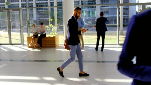blandad ras affärs man ringa i lobbyn på kontoret 4k - kostym sida bildbanksvideor och videomaterial från bakom kulisserna
