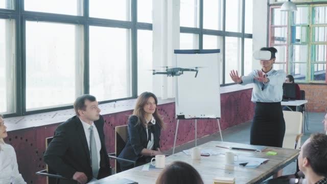 男女混合の女性エンジニアが手のジェスチャーとVRヘッドセットでドローンを制御します。成功。従業員は手をたたいてお互いを祝福します。コワーキングスタートアップチーム。新技術 ビデオ