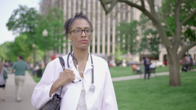 Mixed-Race Female Medical Professional Walks in an Urban Park video