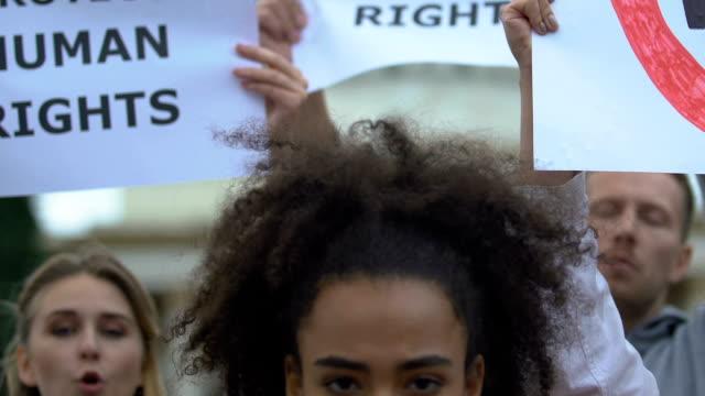 vídeos de stock, filmes e b-roll de menina da misturado-raça que prende nenhum sinal do racismo, activistas que acenam bandeiras dos direitos humanos - consciência negra