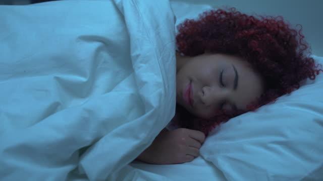 mixed-race woman sleeping in bed, covered with blanket, orthopedic mattress - drzemać filmów i materiałów b-roll