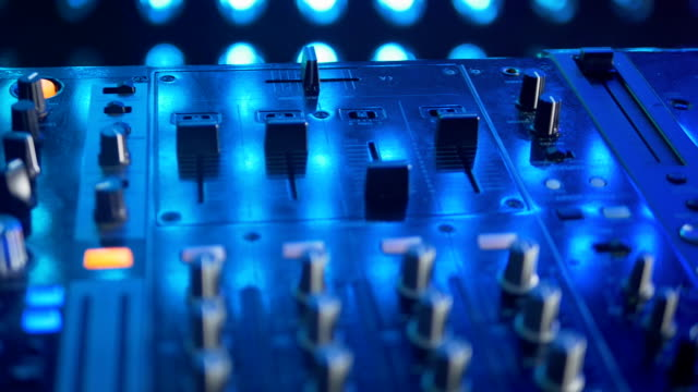 A DJ mixer illuminated by colorful lights. video