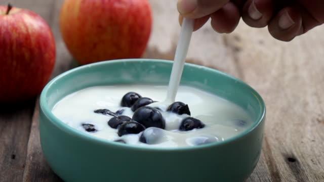 ヨーグルトスローモーションでブルーベリーの果実を混ぜる - パフェ点の映像素材/bロール