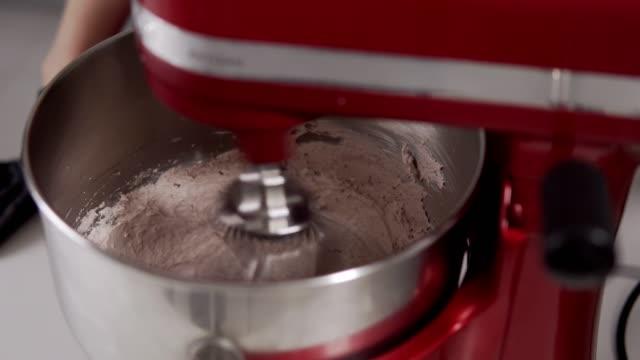 vidéos et rushes de mélanger la crème avec le mélangeur. cuisson de la pâte à crème avec mélangeur rouge. crème pour le gâteau - batteur électrique