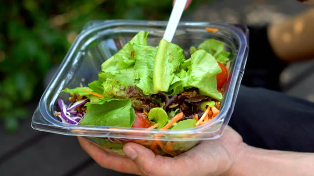 mixing delicious healthy salad in take away plastic container and then eating it - insalata video stock e b–roll