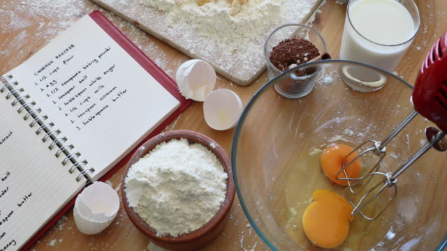 mixing eggs with electric mixer mixing eggs with electric mixer on a wooden table with the flour milk cocoa eggshells cookbook recipe ingredient stock videos & royalty-free footage