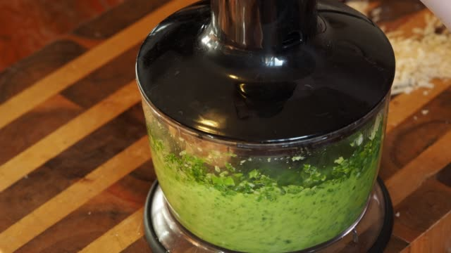 mixing grinded green basil leaves, nuts and cheese in oil cooking of italian Pesto sauce - mixing grinded green basil leaves, nuts and cheese in oil in kitchen blender pesto sauce stock videos & royalty-free footage