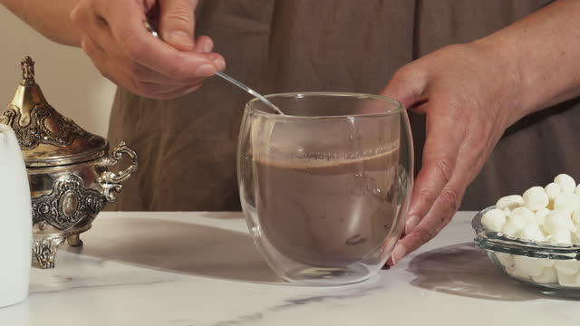 Mixing hot chocolate drink in a glass cup, close up video, marble background