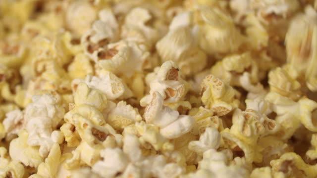 mixing hot popcorn in heap. close up of fresh popcorn flakes. popping up popcorn - готовый к употреблению стоковые видео и кадры b-roll