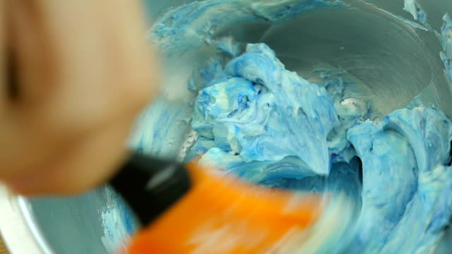 Mixing light blue color to the butter cream .Close up. Slow motion.