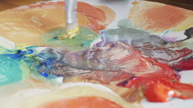 mixing the paint in slow motion. - tavolozza video stock e b–roll