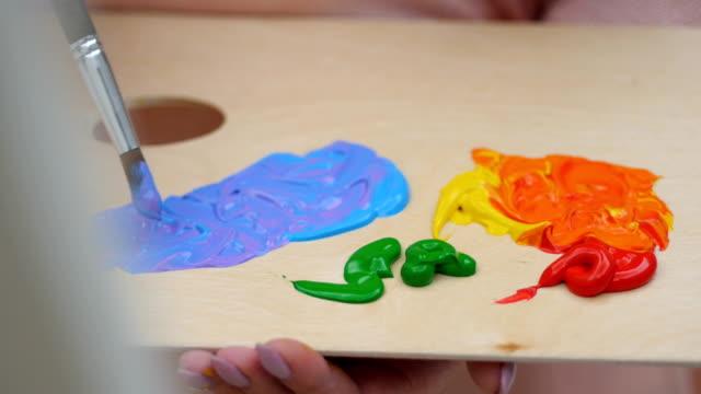 vidéos et rushes de mélange des couleurs dans la palette. pas de visage. 4k. - toile à peindre