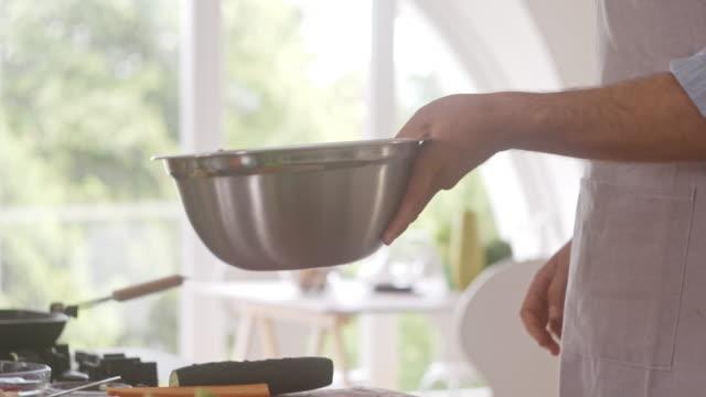 Mixing vegetables in a bowl, preparing salad Mixing sliced vegetables in a bowl, preparing healthy salad, slow motion 4K shot. salad bowl stock videos & royalty-free footage