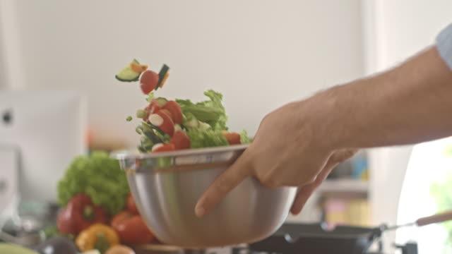 Mixing vegetables in a bowl, preparing salad video