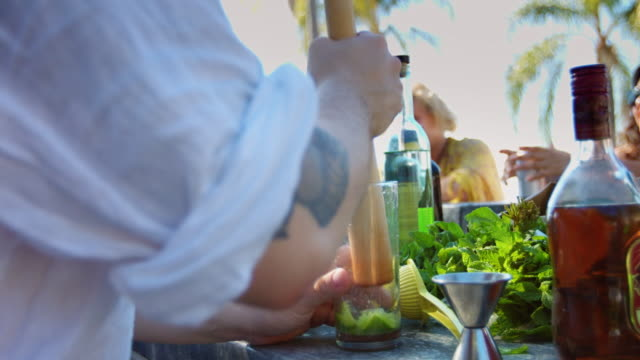 Mixologist Crushing Lime Wedges at Outdoor Pool Party video