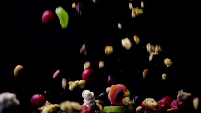 A mixture of dried fruits and nuts with muesli falls on the table slow motion