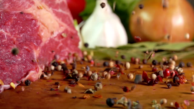 Mixture of peppers falling on a wooden surface Mixture of peppers falling on a wooden surface on a background of meat seared stock videos & royalty-free footage