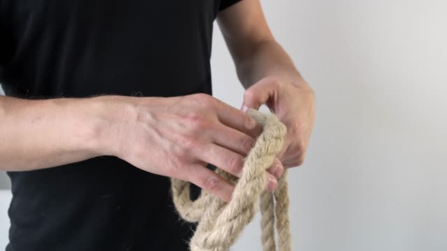 MMn shows how to tie reef knots on hand. Close up