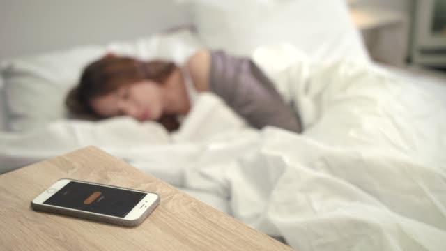 mobil larm vakna upp kvinna i sängen. vakna tid på morgonen. kvinna ny dag - alarm clock bildbanksvideor och videomaterial från bakom kulisserna