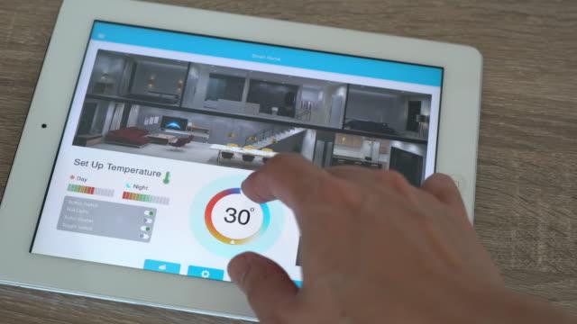 applicazione mobile per domotica e tecnologia smart home - regolazione della temperatura - elettrodomestico attrezzatura domestica video stock e b–roll