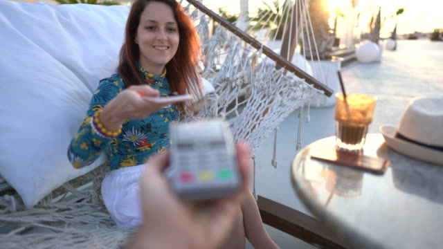 Mobile payment Tourist on the beach bar paying contactless with smartphone credit card purchase stock videos & royalty-free footage