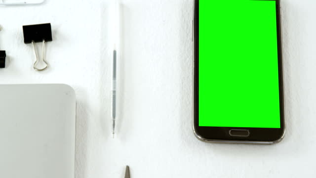 Mobile phone, scissors, bow tie, laptop and paper clip on white background 4k video