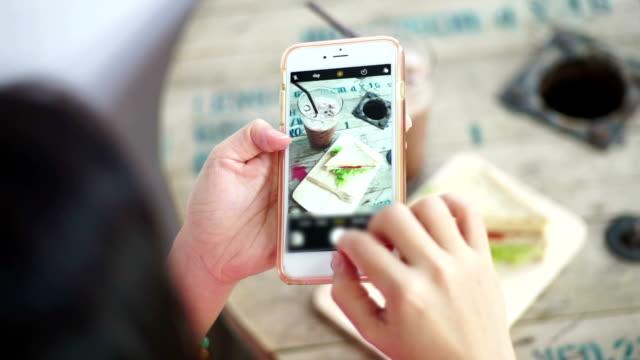 meer: mobil telefonieren, frauen, die aufnahme des frühstücks mit eisschokolade auf holztisch mit smartphone. - fotografisches bild stock-videos und b-roll-filmmaterial