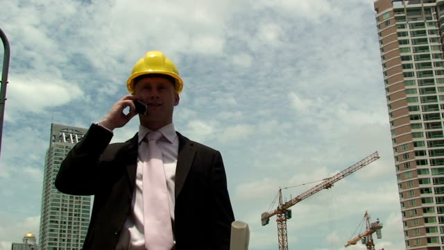 Mobile Phone A construction worker talks on the telephone. craftsman architecture stock videos & royalty-free footage