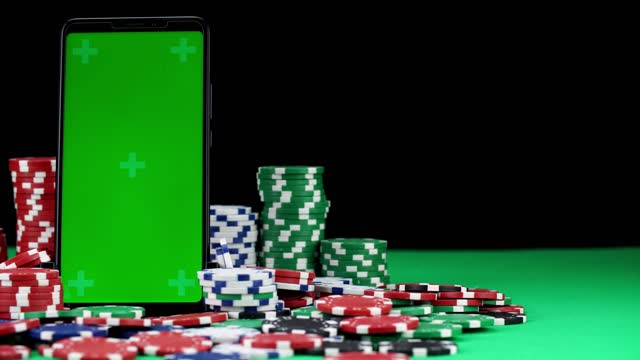 Mobile with green screen in a vertical orientation stands among stacks of poker chips in close-up