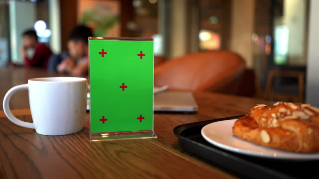 Mock up green signboard in acrylic and snack on table