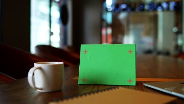 Mock up green signboard tent card menu on wooden table