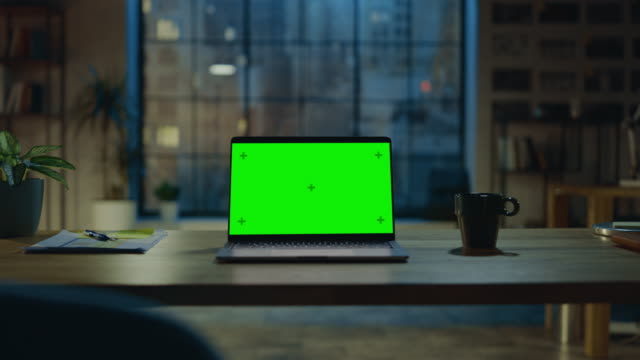 Mock-up Green Screen Laptop Standing on the Desk in the Modern Creative Office. In the Background Warm Evening Lighting and Open Space Studio with City Window View. Zoom in Shot