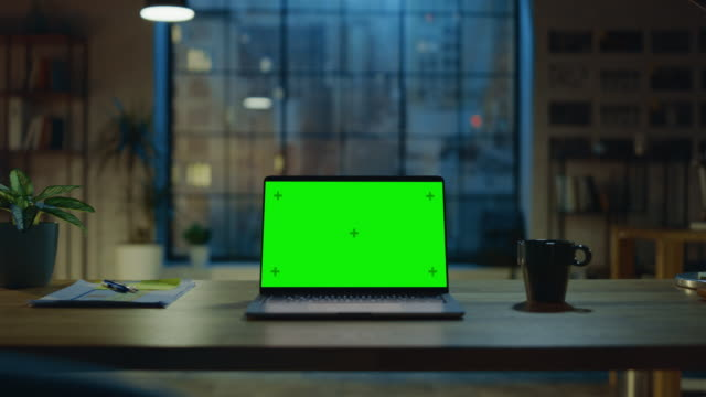 현대 크리에이티브 오피스의 책상에 서있는 모형 녹색 화면 노트북. 배경 따뜻한 저녁 조명과 도시 창보기와 열린 공간 스튜디오에서. 확대/축소 샷 - 책상 스톡 비디오 및 b-롤 화면