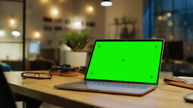 vidéos et rushes de mock-up écran vert stanting sur le bureau. dans le background stylish modern office studio dans la soirée avec big cityscape window - table bois