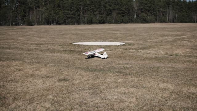 Model aircraft takes off into the sky from the field