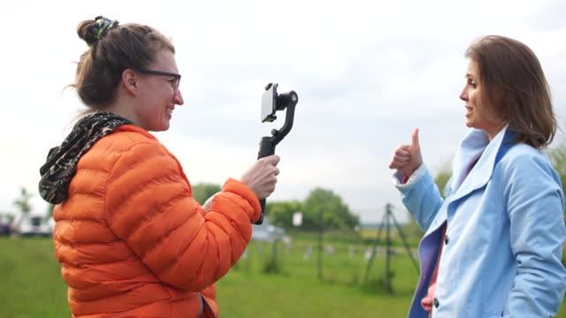 modell och operatör med smartphone och stabilisator. skapa innehåll för en videoblogg. två kvinnor gör videor i parken. tummen upp som gest - filma bildbanksvideor och videomaterial från bakom kulisserna