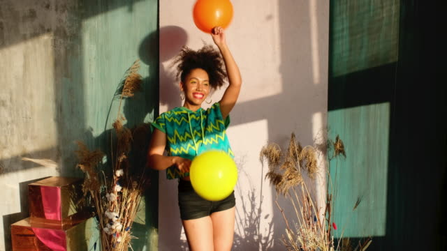 vídeos de stock e filmes b-roll de model dancing with balloons in his hands - mulher balões