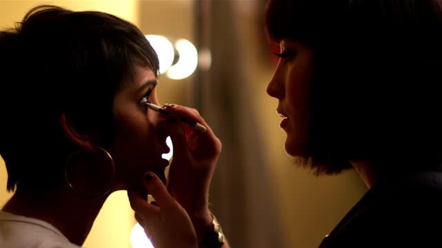 Model getting eyeliner applied video