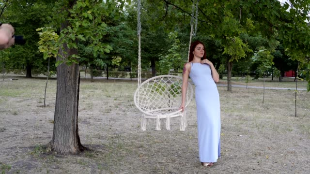 Model girl posing for two photographers in the Park at sunset, in a blue dress near the white swing. Fashion photoshoot outdoors. The view from the outside. Close-up. 4K.