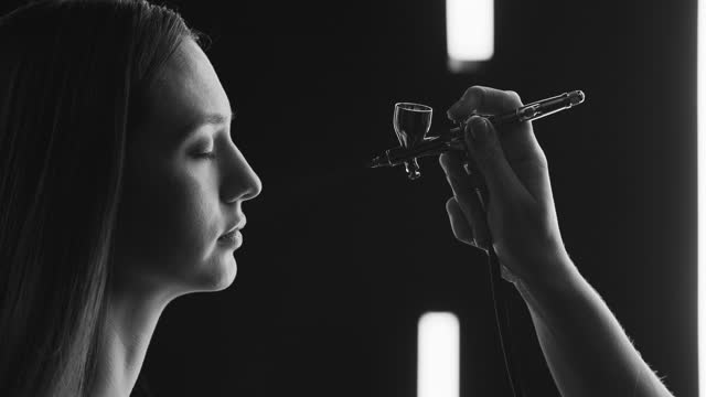 A model girl sits on a lighting office and a make-up artist applies a tonal foundation to her face with an airbrush. Black and white video. video