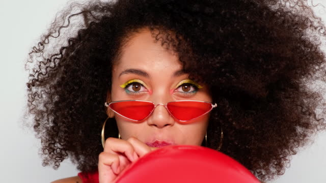 vídeos de stock e filmes b-roll de model inflates a red ball on white background - mulher balões