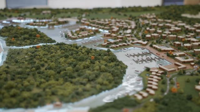 Model Of Urban Development With Buildings Homes Park Harbor Sea Architecture design studio with plastic model and mock-up of new buildings in city area. Close-up of urban development with houses, homes, marina, port, park and sea craftsman architecture stock videos & royalty-free footage